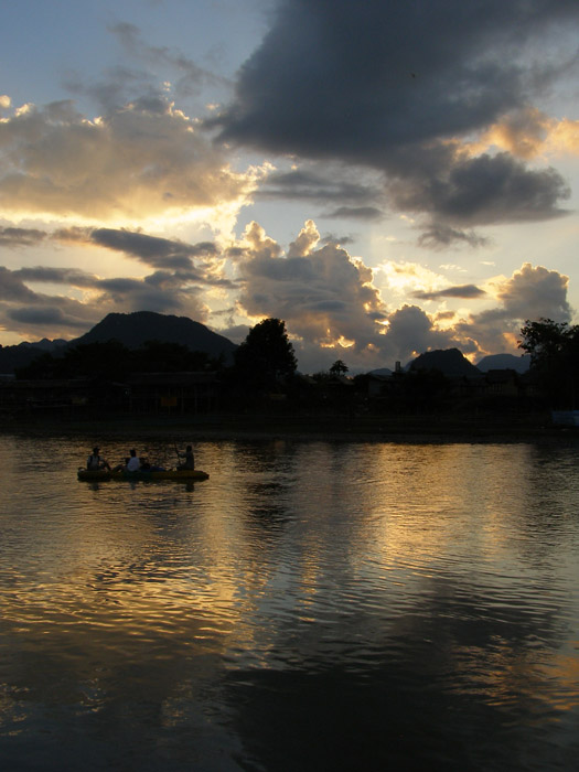 Tourists on the river in front of a Vang Vieng sunset