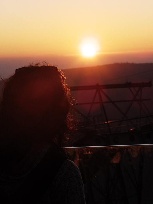 Girl in front of the sunset with lens flare