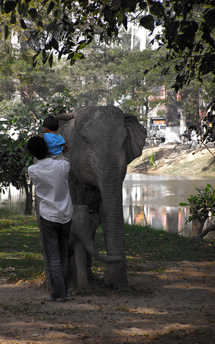 Cambodian man with child and elephant sculpture in Siem Reap